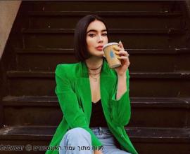 בחורה לובשת מקטורן ירוק ושותה קפה