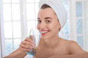 בחורה עם מגבת על הראש שותה מים